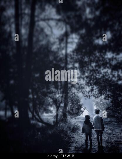 Two children holding hands in a forest - Stock-Bilder