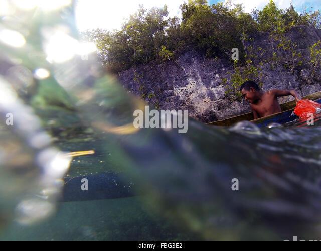 Boy baling to keep old dugout canoe afloat, Gam Island, Raja Ampat, West Papua, Indonesia - Stock Image