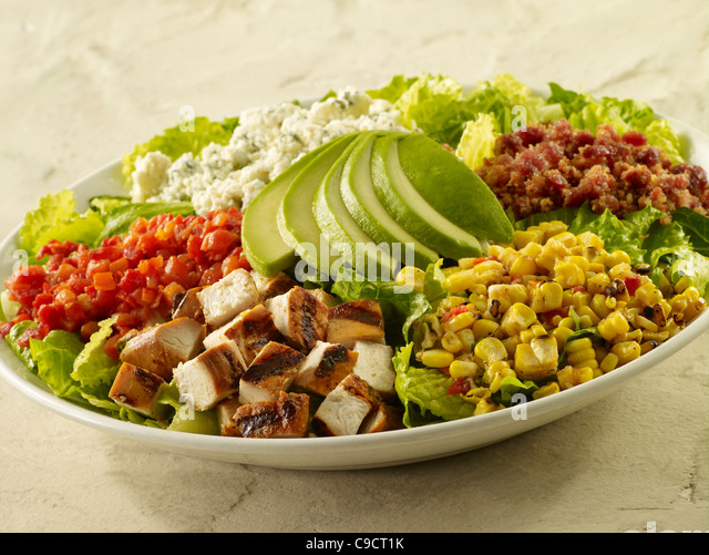 Chopped grilled chicken salad with bacon, corn, cheese, tomato, lettuce and sliced avocado - Stock Image
