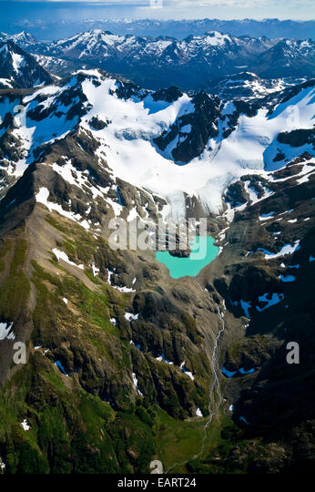 A remote turquoise glacial lake cradled by snow and ice draped peaks. - Stock-Bilder