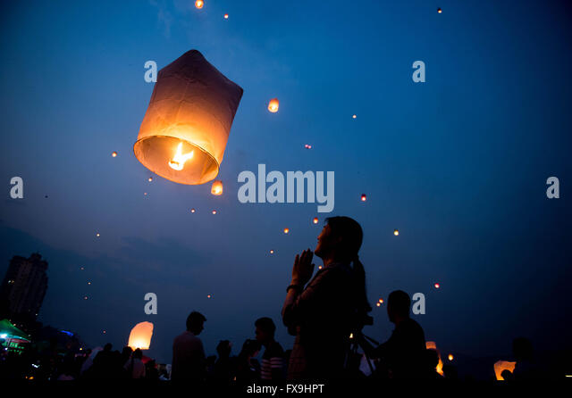 Jinghong. 13th Apr, 2016. A woman makes a wish after she sets a sky lantern into the air along the Lancang River - Stock Image