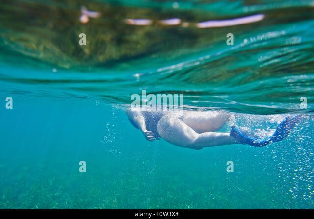 Snorkeler swimming underwater - Stock Image