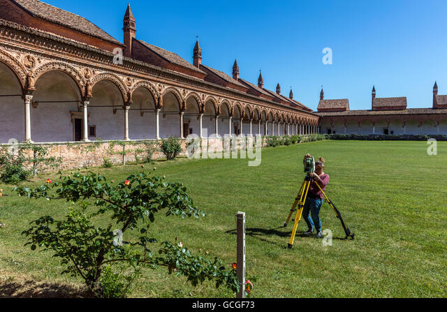 Female surveyor conducting a survey with the Leica Total Station at the Grand Cloister of the Certosa di Pavia monastery - Stock Image
