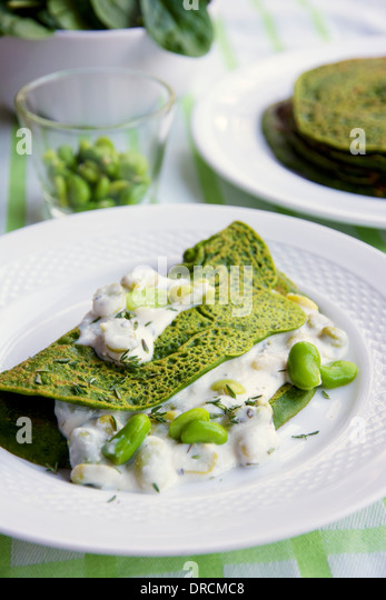 Green Pancakes with creamy fava beans. - Stock Image