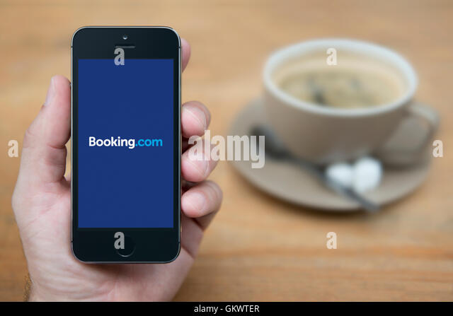 A man looks at his iPhone which displays the Booking.com logo, while sat with a cup of coffee (Editorial use only). - Stock Image