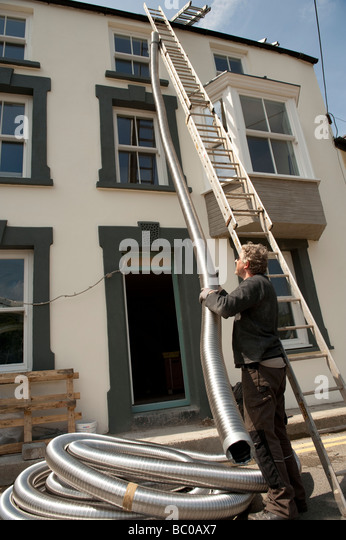 A man installing flexible metal chimney flue liner to a house for a wood burning stove - Stock Image