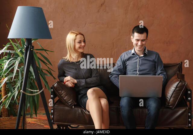 Middle Eastern couple sitting on sofa using laptop - Stock-Bilder