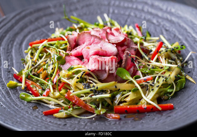 Authentic salad with bacon fresh red pepper, sprouts, sesame and olive oil on a black plate. Morning atmospheric - Stock Image