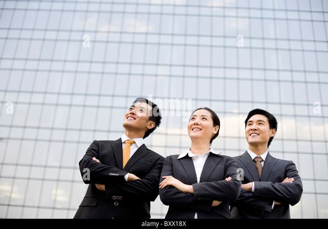 Business team in front of a tall building - Stock Image
