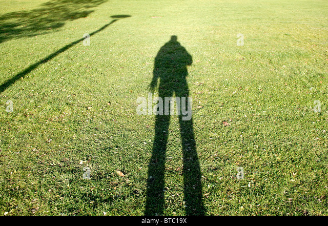 PHOTOGRAPHER SHADOW ON LAWN - Stock Image