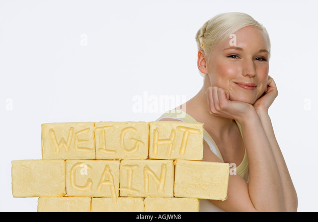 Young woman with blocks of butter - Stock Image