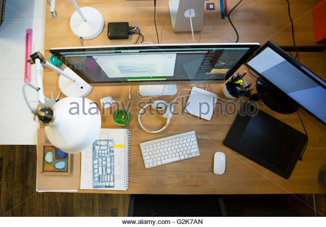Overhead view of computers and digital tablet on desk - Stock Image