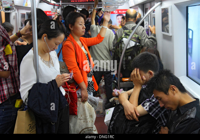 Beijing China Nanlishilu Subway Station Line 1 public transportation train cabin passengers riders standing Asian - Stock Image