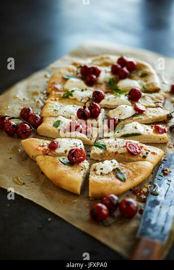 homemade pizza with cherry tomatoes - Stock Image