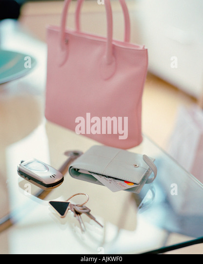 Purse handbag cell phone and keys on a table - Stock Image