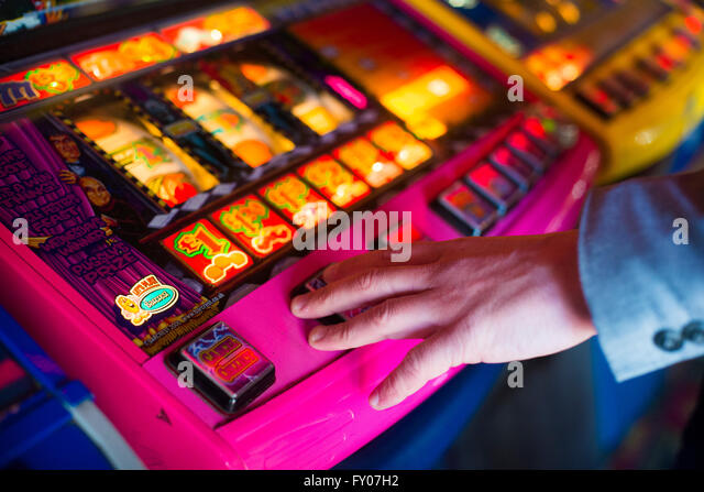 a man's hand on a fruit machine gambling - Stock Image