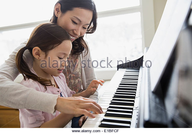 Mother teaching daughter to play piano - Stock-Bilder