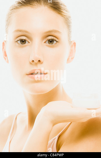 Young woman holding jar of moisturizer, portrait - Stock Image