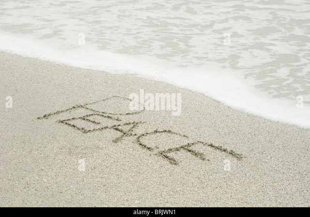 The word 'peace' written in the sand at the beach - Stock-Bilder