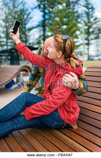 Australia, Queensland, Mid-adult couple taking selfie - Stock Image