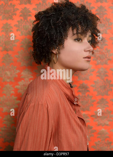Porraits of people in front of orange wallpaper - Stock Image