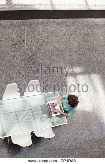 Businesswoman using laptop at conference table - Stock-Bilder