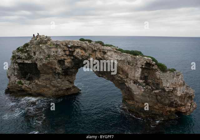 Tourists on natural arch in sea - Stock Image
