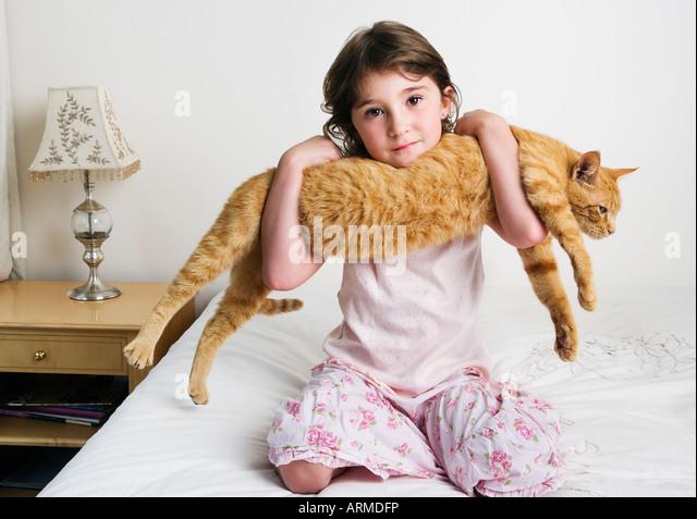 girl holding cat in arms - Stock-Bilder