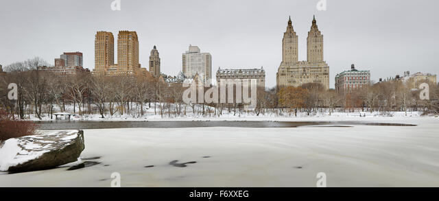 Winter morning after snowfall in Central Park and frozen lake. Manhattan Upper West buildings rise above the park, - Stock Image