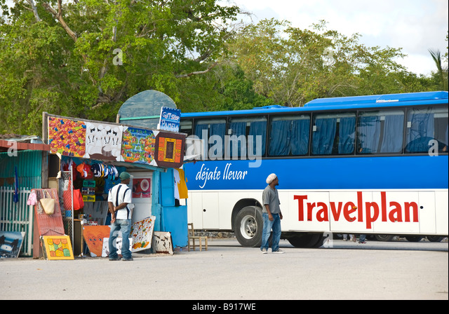 Tour bus at Bayahibe fishing village Dominican Republic southeast coast popular tourist destination for boat trips - Stock Image