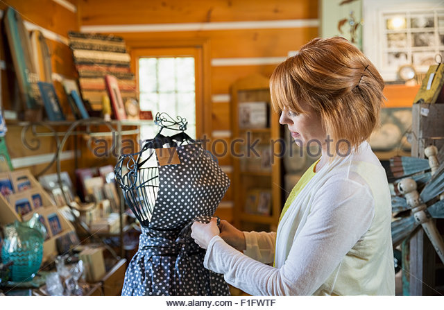 Shop owner preparing apron display - Stock Image