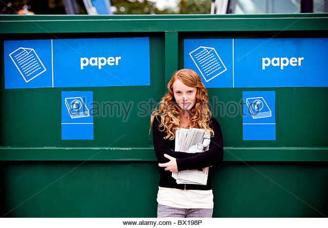 A teenage girl standing next to a recycling container for paper - Stock Image