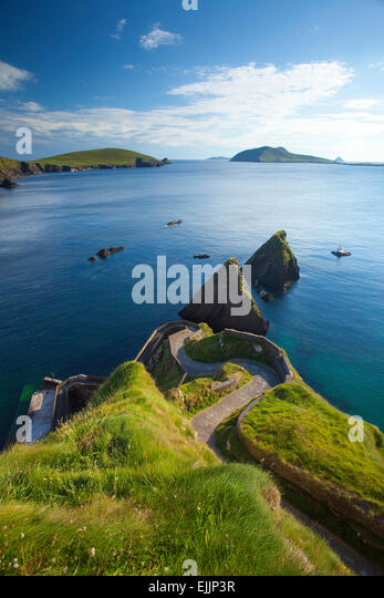 Road descending to Dunquin harbour, with Great Blasket Island in the distance. Dingle Peninsula, County Kerry, Ireland. - Stock Image