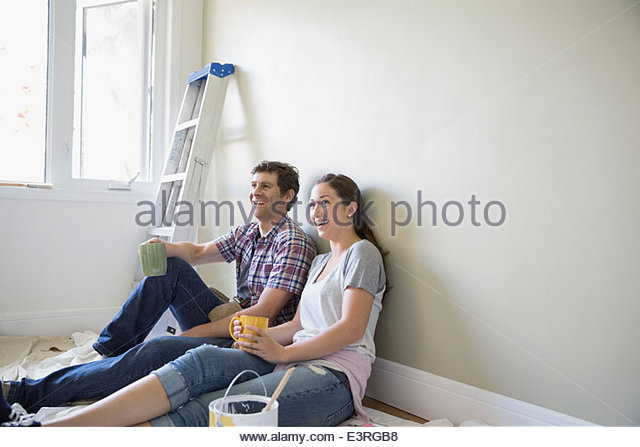 Happy couple drinking coffee on paint drop cloth - Stock Image