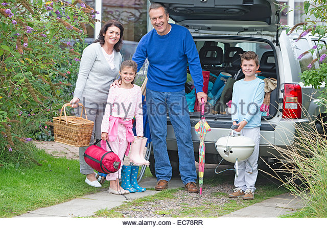 Grandparents and grandchildren packing car for vacation - Stock-Bilder