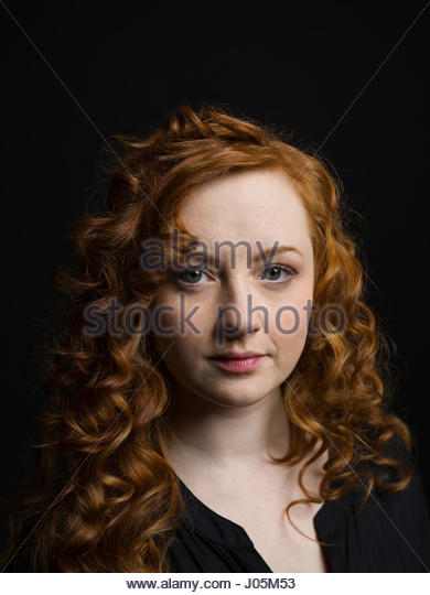 Portrait serious woman with curly red hair against black background - Stock Image