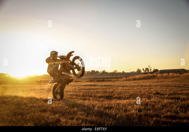 Man riding motorcycle creating dust trail - Stock Image
