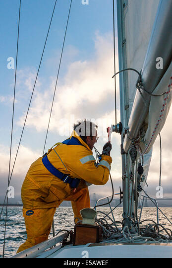 Sailor in yellow foul weather gear securing the halyard after raising the mainsail heading into cloudy weather in - Stock Image