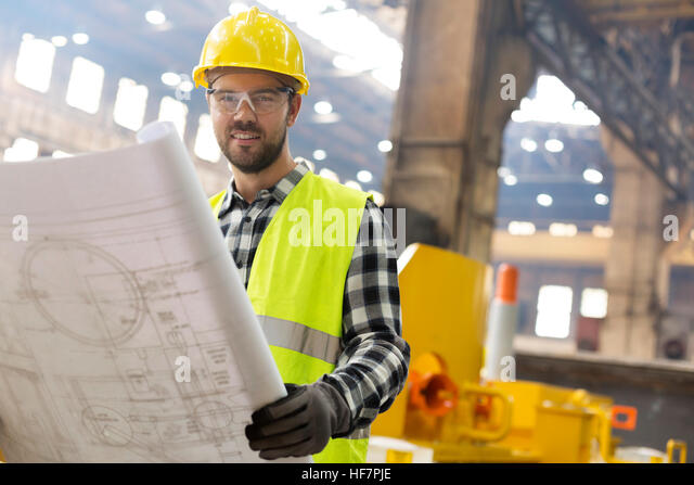 Portrait smiling engineer with blueprints ins steel factory - Stock Image