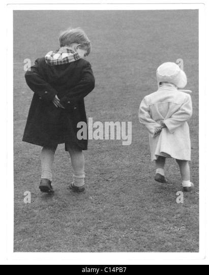 Young children both walking with their hands behind their backs -1950's - Stock Image