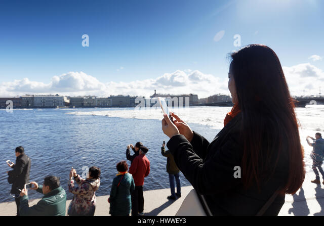 St. Petersburg, Russia, 23rd March, 2017. Chinese tourists make photos on the embankment of river Neva during the - Stock Image