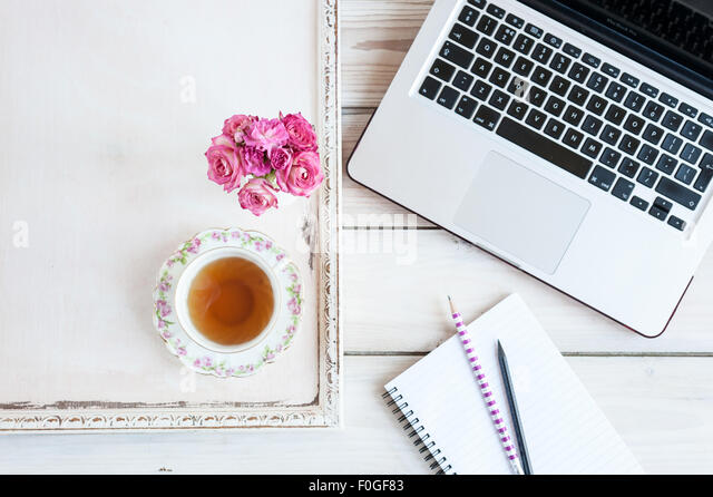 working from home - laptop, notebook, pencils, tea and roses - Stock-Bilder