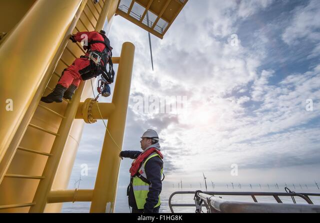 Engineer climbing wind turbine at offshore windfarm - Stock Image