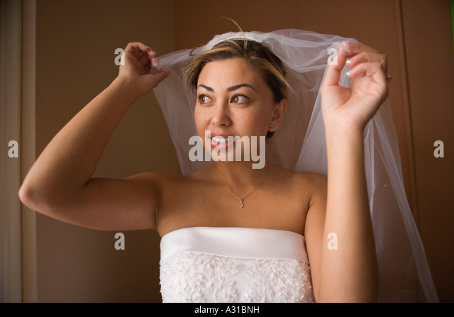 Bride lifting veil over head and looking out window - Stock-Bilder