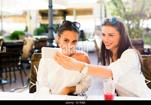 Two young beautiful women taking a selfie of themselves during lunch break - Stock Image