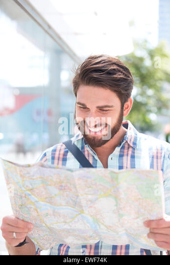 Happy man reading road map in city - Stock Image