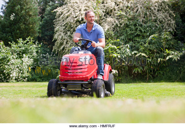 Man driving ride on mower, mowing grass in sunny summer yard - Stock-Bilder