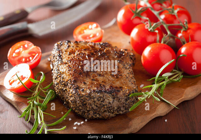beef steak with spices and rosemary on wooden background - Stock Image