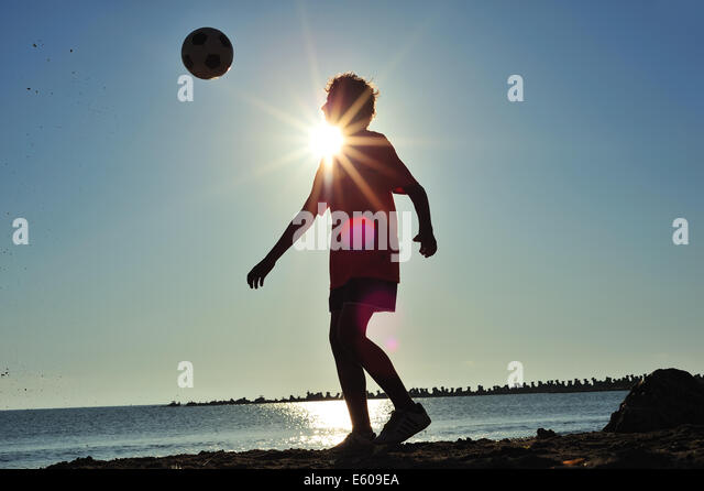 Boy playing football on beach at sunset - Stock Image