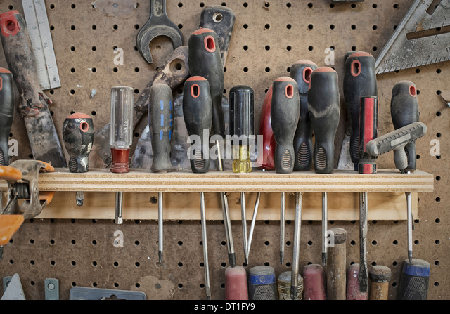 A reclaimed lumber workshop A tool board with slots for screwdrivers and handheld woodworking tools - Stock-Bilder